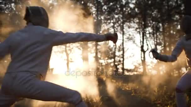 Male and female fencing in the forest wearing full outfit