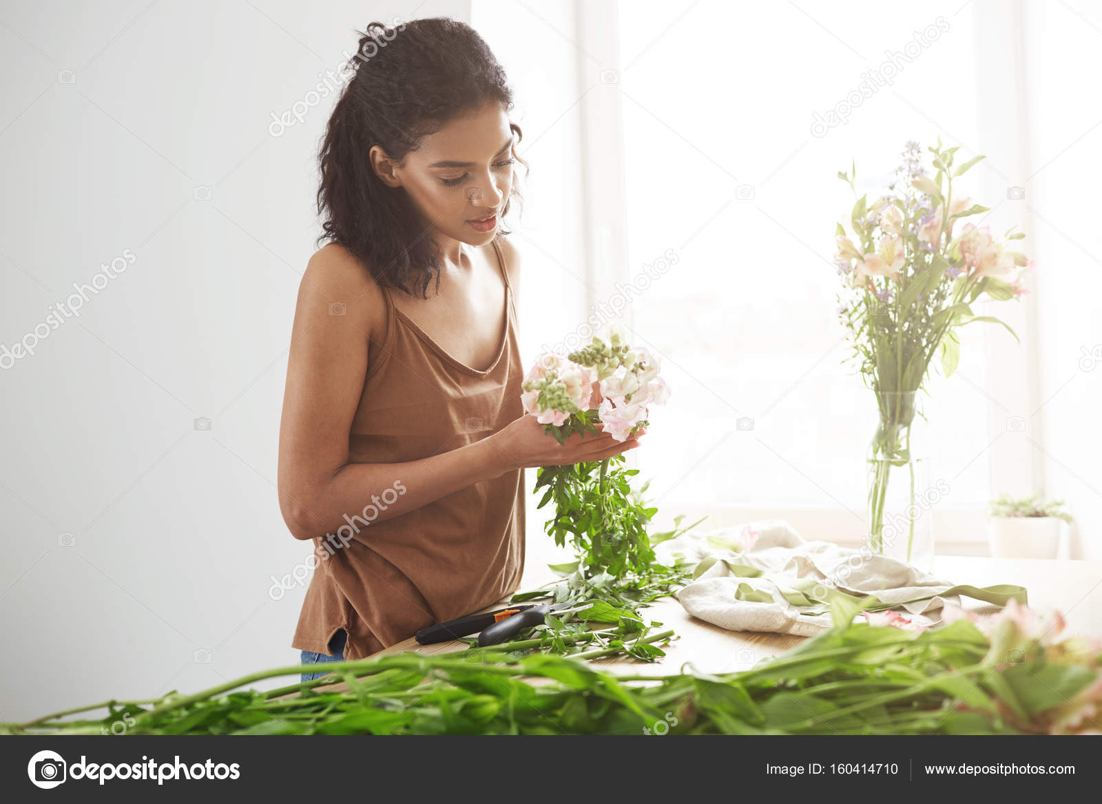 Attractive african girl florist smiling making bouquet of flowers at attractive african girl florist smiling making bouquet of flowers at workplace over white wall copy space nkavchenkoail fotoraf izmirmasajfo