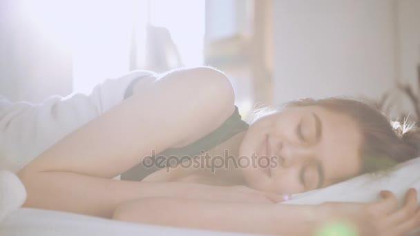 Kavkazský dívky tlouci v posteli v slowmotion. Pojem ráno a spánku. Sluneční erupce