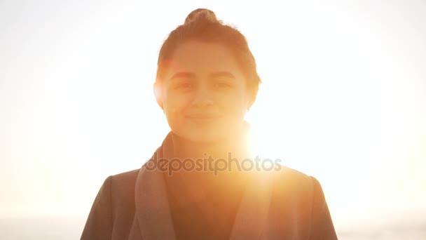 Ritratto di signora goodlooking in piedi contro il mare durante lalba in slowmotion. Chiarore del sole