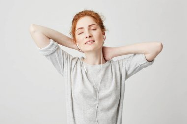 Portrait of tender beautiful redhead girl listening to music in headphones with closed eyes smiling enjoying over white background. Hands behind head.