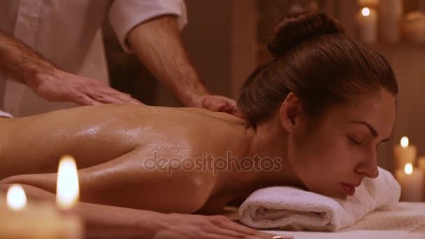 Atraktivní žena ležící na lehátku v lázeňském středisku v slowmotion. Koncepce zdraví a relaxace