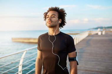 Portrait of fit dark-skinned muscular man runner with bushy hairstyle looking concentrated in black sport clothing wearing white earphones. Sports, fitness and healthy lifestyle.