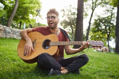 Stylish guy with pierced ear wearing trendy sunglasses and red t-shirt singing songs and playing guitar, sitting on grass in park.