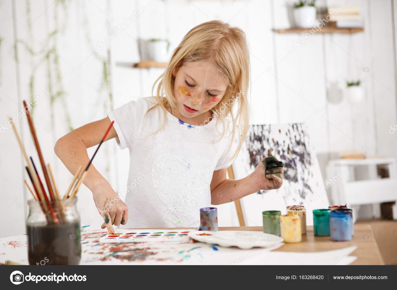 Creatieve mooie vrouwelijke kind met blonde haren workinh op haar