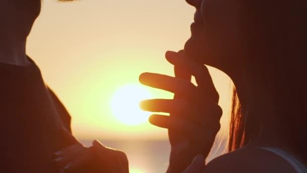 extrémní closeup Romantický guy objímání a dojemné Zenske bradu a dívka drží za ruce na prsou se sluncem na pozadí zpomalené. romantické chvíle