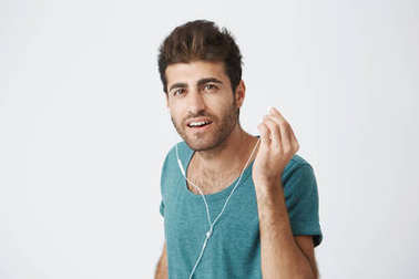 Close up portrait of handsome italian guy in trendy blue t-shirt. listening music and taking off one headphone with hand, trying to hear what his friend said.