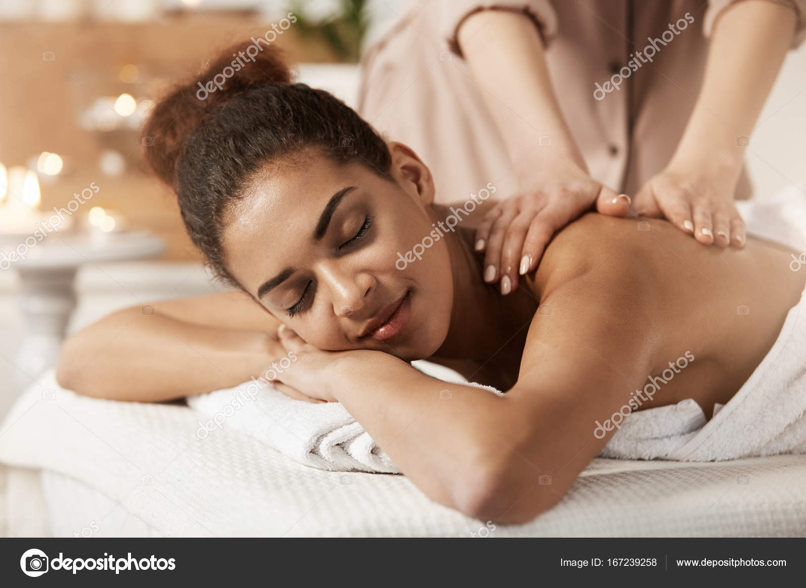 attractive african girl having massage relaxing in spa salon. closed