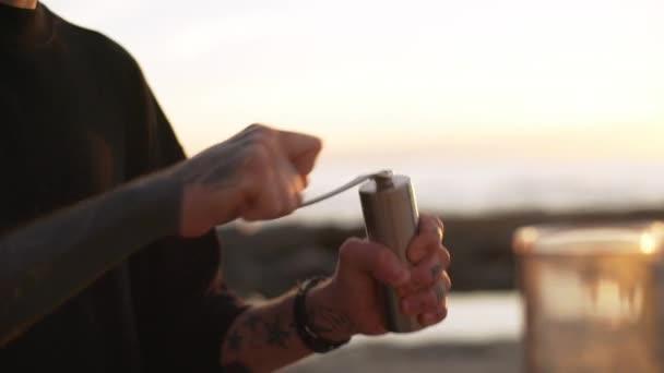 Closeup kaukasischen glücklich lächelnd mahlen Kaffeebohnen mit Hände in manuelle Coffeemill im Freien bei Sonnenaufgang Zeit Zeitlupe