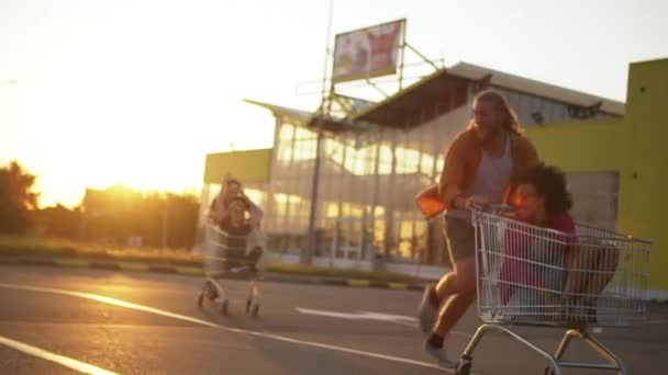 multiethnic young people having fun in mall parking lot in bright day racing with shopping cart enjoying free time slomo