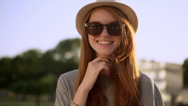 docela zázvor mladá žena v klobouku a sluneční brýle pózuje s velkým úsměvem na fotoaparát mimo slomo closeup