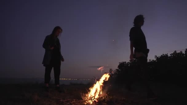 young multiethic friends staying around bonfire warming hands on edge over sea enjoying magic moment together at night slow motion