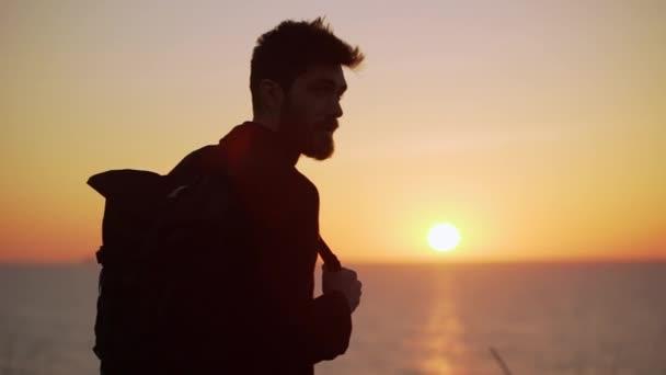 90a4681b01 Hombre atractivo de pie contra la elevación del sol sonriente mirando a un  lado la iluminación de fondo lenta– metraje de stock
