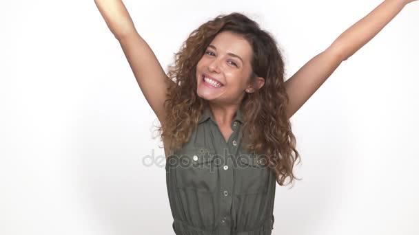 junge energische lockige Frau, die plötzlich vor der Kamera erscheint und glücklich lächelnd isoliert auf weißem Hintergrund tanzt. Konzept der Emotionen