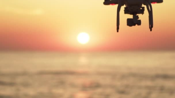 in slow motion silhouette of drone flying close to sun over calm sea with captivating golden sunrise and flying birds background