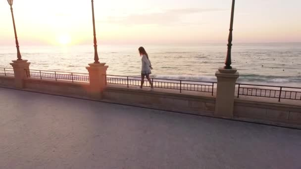 slomo from drone young woman with long hair in white outfit walking along parapet of embankment balancing backside with empty beach background on sunrise