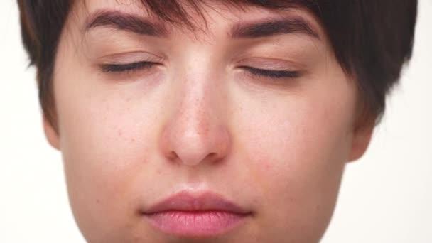 extrémní zblízka portrét mladé dámy zelené oči při pohledu na fotoaparát s úsměvem izolované na bílém pozadí. Pojetí emocí
