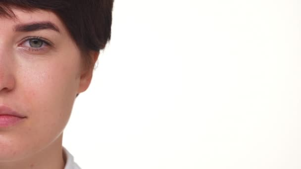 Side portrait of nice short-haired girl opening eyes isolated over white background extreme closeup slomo. Concept of emotions
