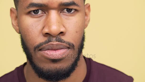 extrémní closeup portrét jistý afroamerické kluka s hnědýma očima nosit sportovní oblečení přísně prohlíží fotoaparátu bliká stojící nad žlutým pozadím slomo. Pojetí emocí