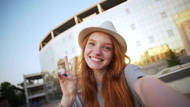 okouzlující zázvor dívka v klobouku, když selfie video baví blbnout ukazuje míru s detailním stadion slomo pozadí
