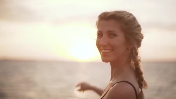 Kavkazská blondýnka úsměvy zapne kamera ukazuje na slunci s rukou. Zpomalený pohyb, slunce