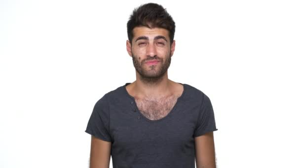 handsome guy wearing grey t-shirt nodding positively smiling broadly with white teeth feeling excited showing index finger on camera over white background. Concept of emotions