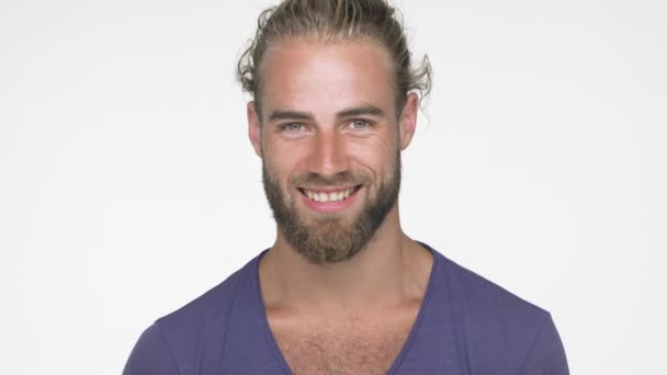 closeup caucasian handsome man wearing blue t-shirt looking at camera smiling broadly with white teeth nodding positively over white background. Concept of emotions