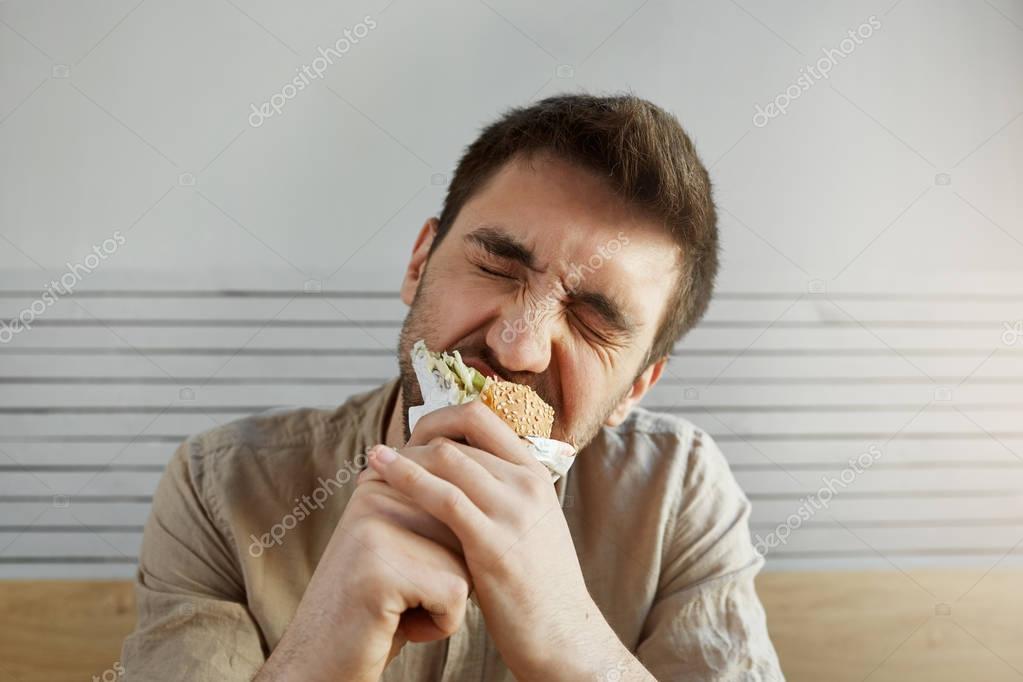 Junge unrasierte schöner Kerl mit dunklen Haaren Sandwich ...