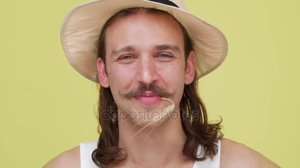 dlouhé tmavé vlasy šťastnej chlap s krásným úsměvem v béžový klobouk zapouští kořeny v jeho ústech nad žlutým pozadím closeup. Koncepce emocí v pomalém pohybu