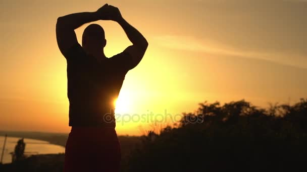 picture from back silhouette of muscular strong bald man in black T-shirt standing on top of hill looking at sea stretching arms warming up in summer slow motion