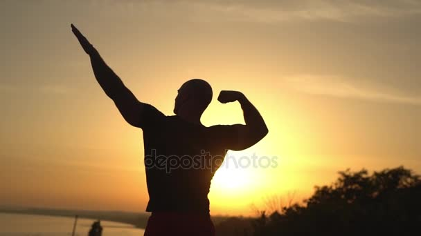picture from back silhouette of muscular strong bald man standing on top of hill looking at sea showing biceps putting arms up in air doing athletic gestures in summer slow motion