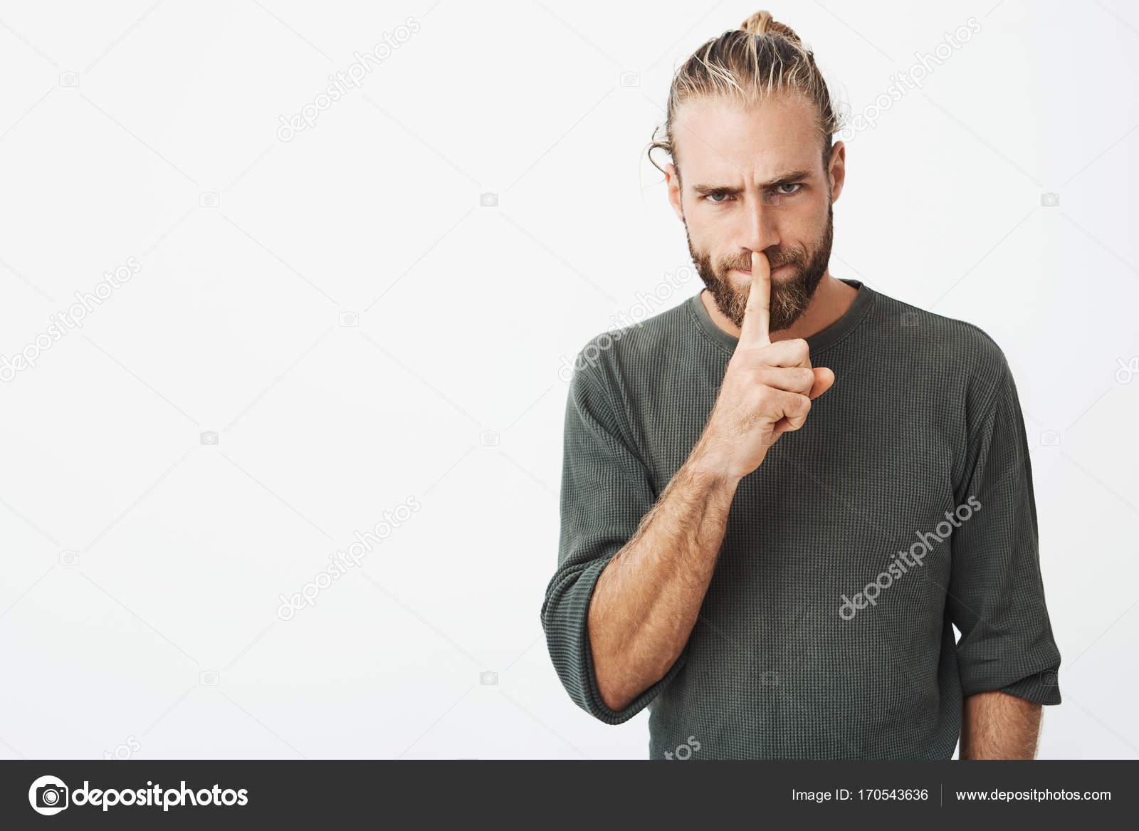 Porträt von modischen jungen Mann mit Finger auf die Lippen mit ...
