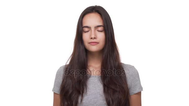portrait of calm young woman with long dark hair opening eyes and looking at camera isolated over white background closeup. Concept of emotions