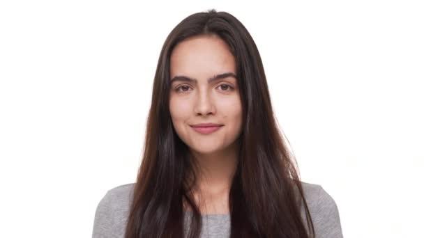 portrét okouzlující šťastné ženské model s dlouhými tmavými vlasy při pohledu kamery s úsměvem, izolované na bílém pozadí closeup. Pojetí emocí