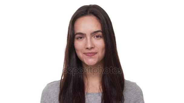 hosszú haj nézett mosolyogva integetett kézzel, mondván: Szia felett fehér háttér Vértes barátságos kamera pozitív barna nő portréja. Az érzelmek fogalma