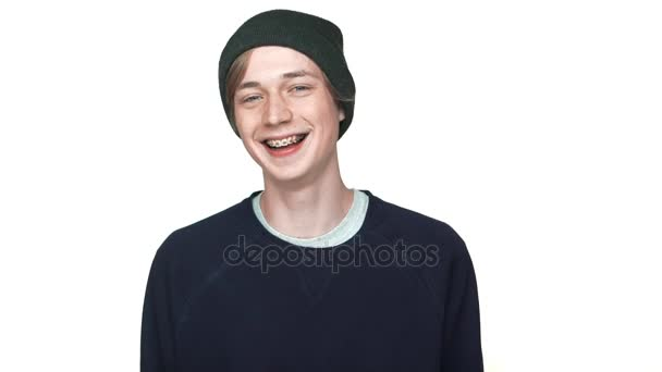 slowmotion portrait of happy teenage boy in braces wearing hat laughing smiling on camera isolated over white background closeup. Concept of emotions
