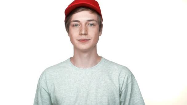 lassú mozgás portréja pozitív csípő tinédzser visel piros sapkát és szürke póló mosolygó találat hüvelykujj-fel, hogy a fehér háttér Vértes örülök, hogy jó hangulatban. Az érzelmek fogalma