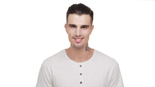 headshot of attractive stylish tattooed man with bristle looking on camera smiling with teeth laughing expressing joy over white background in studio closeup. Concept of emotions