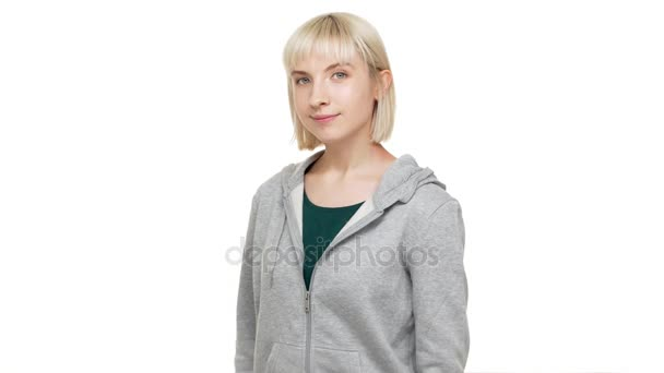 half-turn closeup portrait of caucasian candid female blondie having blue eyes in sweatshirt looking at camera showing thumb up gesturing like sign isolated over white background. Concept of emotions
