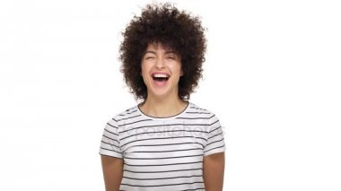Portrait of amazing lovely mixed-race female wearing stripped t-shirt bursting with laughter expressing happiness and joy being isolated over white background in studio. Concept of emotions