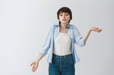 Portrait of beautiful young woman with short haircut gesticulating with hands showing she doesnt understand anything. Body language.