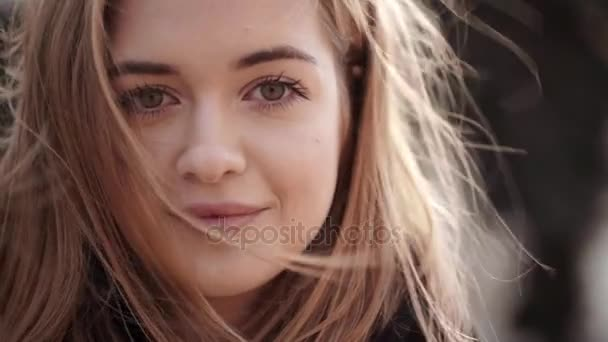 Closeup portrait of attractive female having natural makeup posing on camera and smiling with wind blowing her light brown hair in slow motion. Movie style