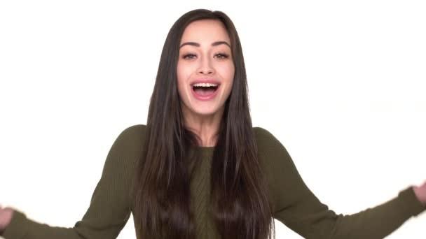 Portrét mladé usmívající se žena 20s exprimují štěstí a překvapení pokrývající otevřená ústa vzrušením nad bílým pozadím. Pojetí emocí