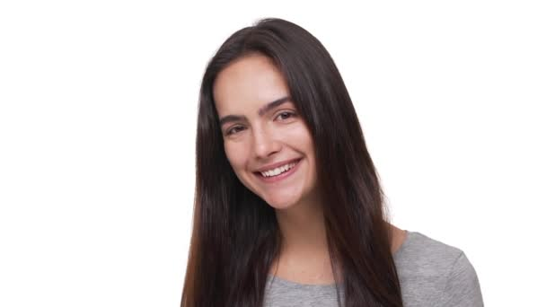 portrait of young joyful woman with long brown hair looking at camera smiling laughing with white teeth isolated over white background closeup in slow motion. Concept of emotions