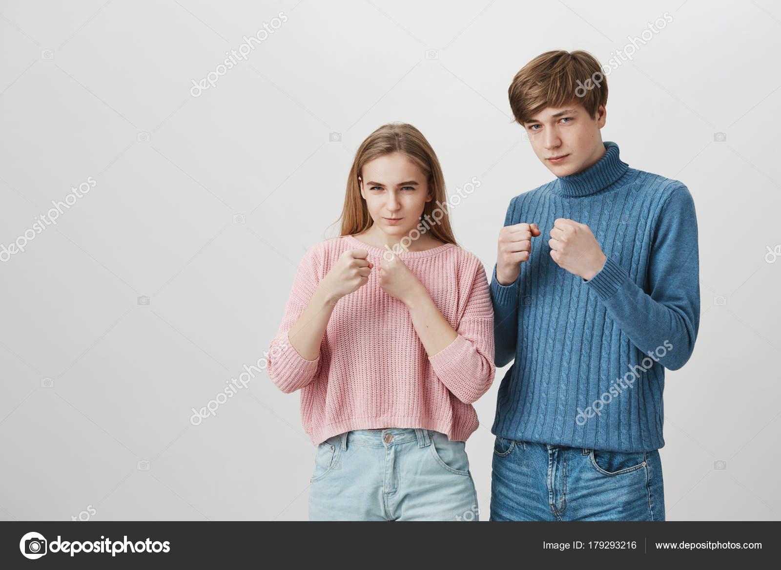 f96d60645 Menina loira e cabelos louro cara em pé dentro de casa com punhos agrupados  e determinadas expressões do rosto. Casal caucasiano em camisolas de malha  ...