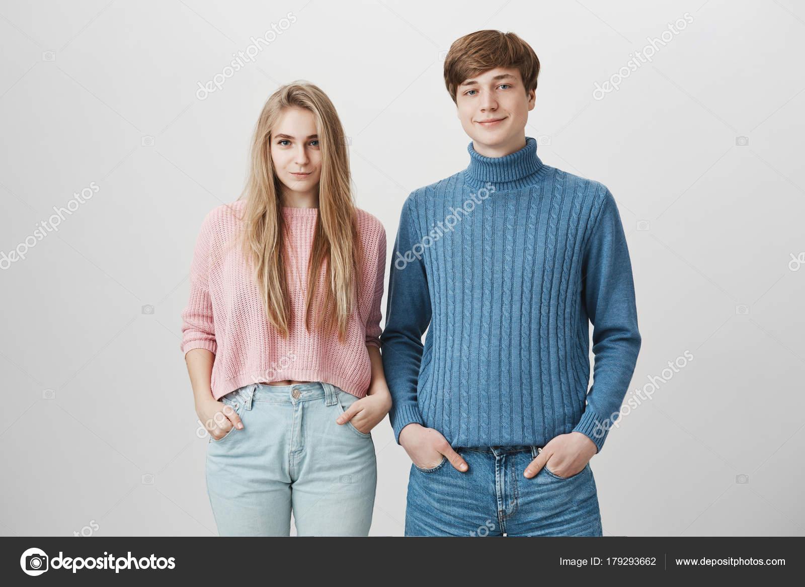 7a935620f Família dose de caucasiano irmão e irmã de pé perto do outro posando dentro  de casa em camisolas de malha coloridas. Positivo-de-olho-azul elegante  jovem ...