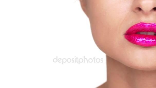Extrémní closeup žena tvář s baculatou růžové rty na kameru s úsměvem ukazuje dokonalé zuby nad bílým pozadím. Výrazy obličeje