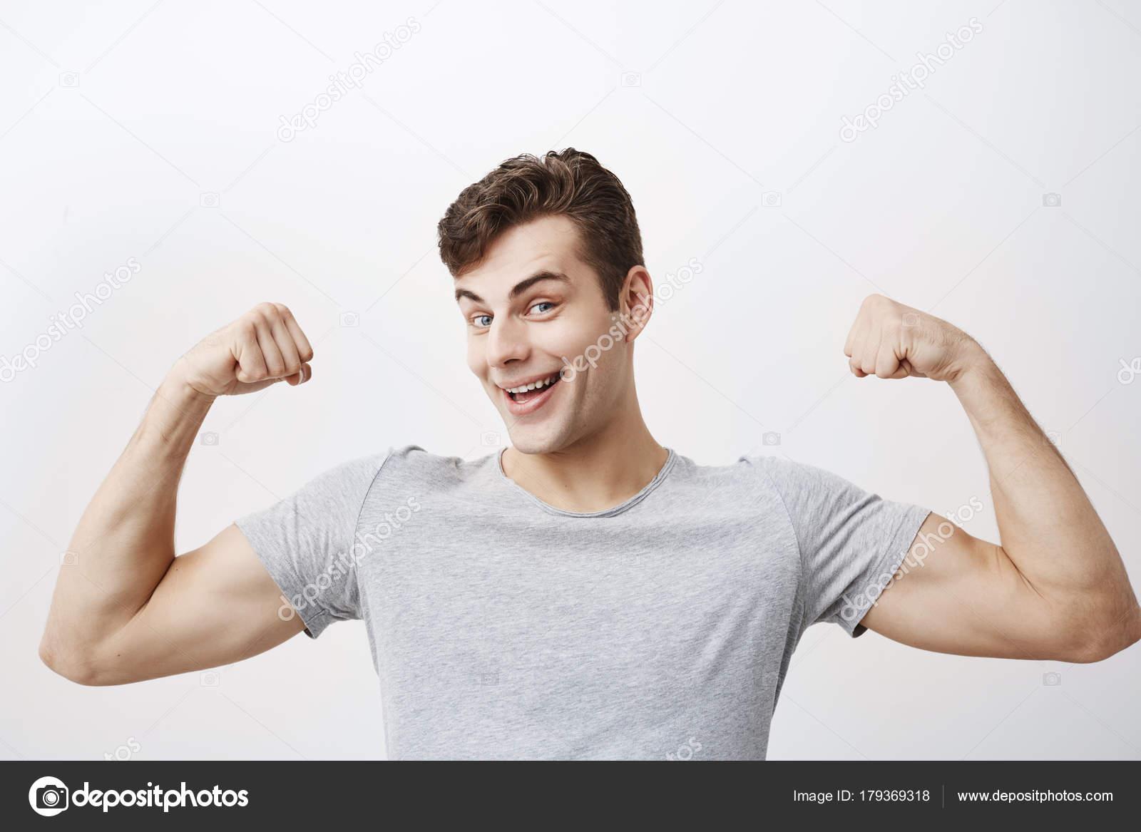 Positive emotionale Mann lächelt, zeigt Muskeln an den Armen, fühlt ...