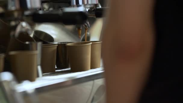 Close up shoot of barista making coffee pouring from espresso machine into two paper cups in slow motion