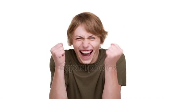 Portrét radostné guy 20s v zelené tričko zaťaté pěsti je vzrušený, choval se jako vítěz nad bílým pozadím ve zpomaleném filmu. Pojetí emocí